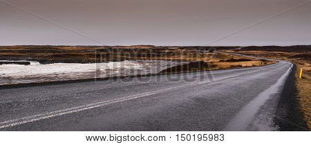 Highway countryside straight road with with icy frozen lake on the side at Snæfellsnes Peninsula in Iceland