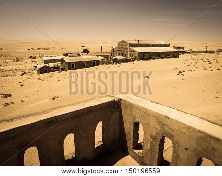 Ghost buildings of old diamond mining town Kolmanskop near Luderitz in Namibia. Abandoned house ruins sunken in the sand dunes of Namib Desert. View from balcony. Vintage toning photography.