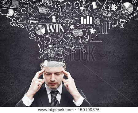 Pensive young businessman with business sketch coming out of his head on concrete background. Brainstorming concept