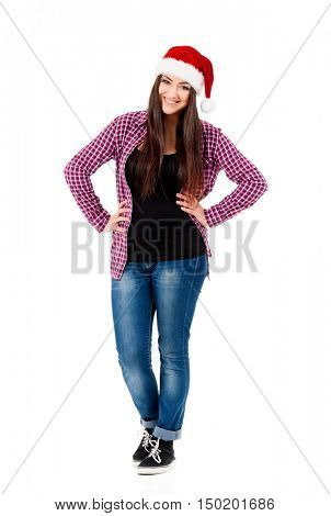 Beautiful caucasian girl wearing christmas hat for santa, looking at camera. Full length portrait of happy young woman wearing Santa Claus hat, isolated on white background.