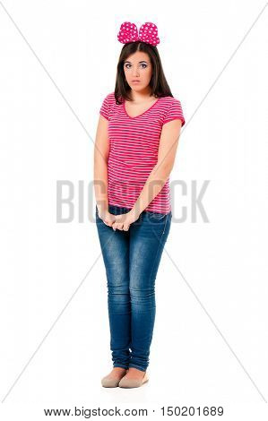 Sad teen girl with big red bow, isolated on white background. Expressive full lenght portrait of young brunette woman with shy gesture and posture.
