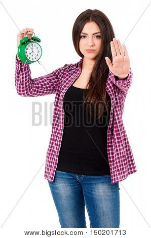 Beautiful teen girl holding big green alarm clock and making stop gesture with her palm, isolated on white background.