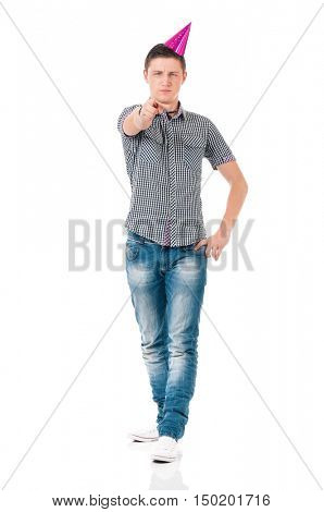 Full length portrait of guy with party hat, isolated on white background. Teen student boy with birthday cap pointing at camera choosing you. Portrait of young man show forefinger to front.