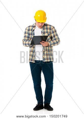 Full lenght portrait of a young architect with yellow hard hat. An engineer or foreman holding clipboard. Young construction worker or businessman wearing helmet, isolated on white background.