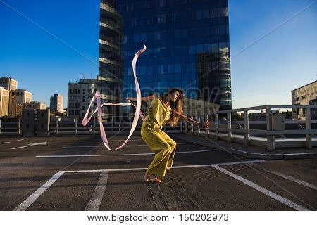 Gymnast girl with ribbon. Professional gymnast woman dancer posing with ribbon on the roof of the building. The skyscraper in the background.