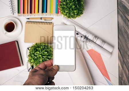 Male hand holding smartphone with blank white screen over modern office desktop. Mock up