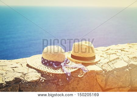 two hats with traditional maltese boats on background, travel in Malta concept