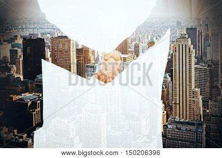 Businesspeople shaking hands on city background. Partnership concept. Double exposure