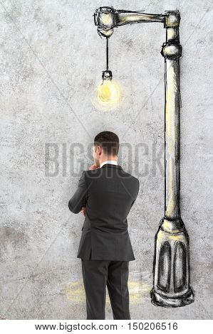 Back view of thoughtful businessman standing against textured concrete background with creative street lamp drawing. Research concept