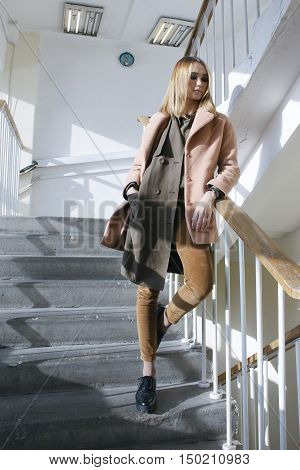 young stylish female in coat stay on stairs