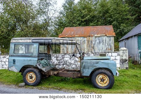 Old rusting abandoned vehicle with peeling paint and no doors sits in front of derelict outbuildings and trees