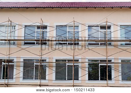 Scaffold around colored two-storey building with large windows
