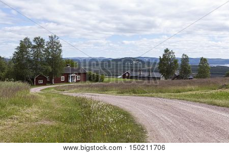 HARJEDALEN, SWEDEN ON JULY 07. View over buildings, gravel road and the landscape on July 07, 2016 in Harjedalen, Sweden. Summer and farmland. Editorial use.