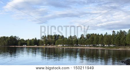 MEDELPAD, SWEDEN ON JULY 09. View of a campsite, car, campers and caravan on July 09, 2016 by Holmsjon, Sweden. Sunny summer day. Pine forest and a lake. Editorial use.