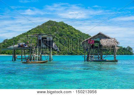 The traditional sea gypsy water village in Bodgaya Island in Tun Sakaran marine park,Semporna,Sabah,Borneo,Malaysia.Clear blue water,sand & palm trees.Beautiful vacation & destination.