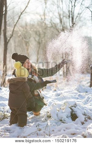 Happy family having fun with snow in the park on a sunny day. Mother with cute toddler child enjoying winter outdoors. Mom with boy. Winter and holidays seasons concept.