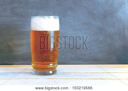 A glass of chilled beer on a white wooden table. Blackboard background composition with an empty copy space for Editor's text.