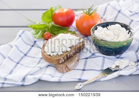 Organic Farming Cottage cheese in a green bowl slice of whole wheat bread with Homemade Ricotta cheese served with tomatoes and basil on wooden board on linen fabric. Healthy food concept
