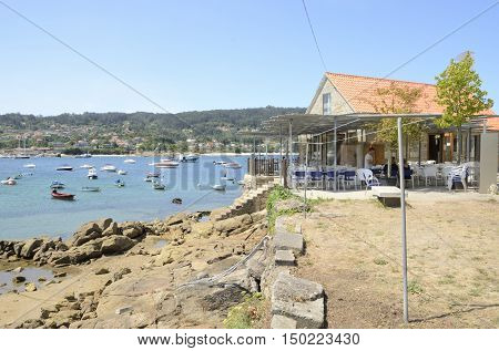 ALDAN, SPAIN - AUGUST 9, 2016: Some people having lunch in the terrace of a restaurant located in the fishing port of Aldan in the province of Pontevedra Galicia Spain.