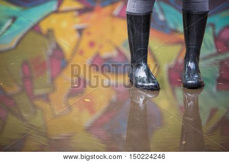 Girl in rubber boots standing in the puddle in the street. Woman in grey rubber boots splashing in a puddle after rain. Pair of grey rubber boots in a big puddle with graffiti reflections.