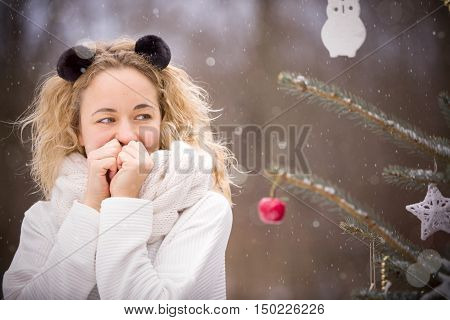 Portrait of smiling young woman with funny headband near a Christmas tree outdoors on a cold winter day. Celebrating holidays and Christmas concept.