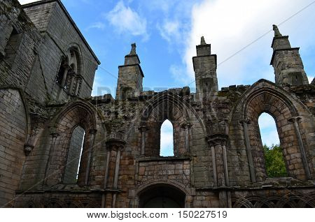 Stone ruins and standing towers of Holyrood Abbey in Scotland.
