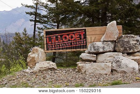 Lillooet BC welcome sign on highway 99 fashioned out of wooden beams and buckshot riddled part of the rockies in the top left on a bright overcast day in April.