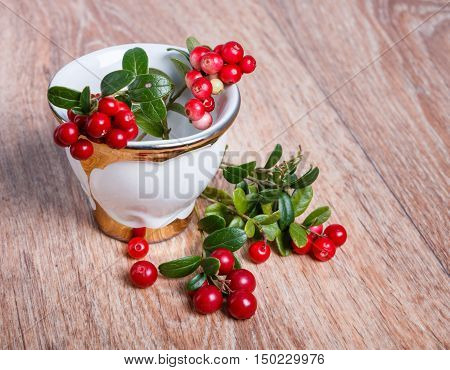 stylish coffee cup and red lingonberries on wooden background