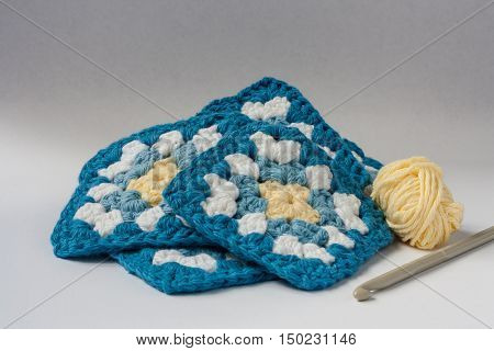 Crocheted granny squares in blue white and yellow with ball of yarn and crochet hook isolated on white