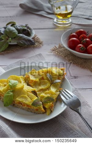 Potato gratin on a white plate with basil tomatoes and olive oil