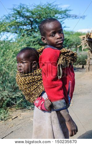 LAKE EYASI, TANZANIA - MAY 29, 2015: Older brother carrying the younger one in a Datoga Tribe at Lake Eyasi Tanzania