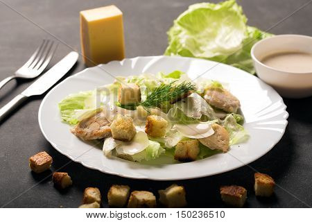 Classical Caesar salad with sliced chicken meat, fresh salad leaves, croutons and sauce in white round plate. Horizontal photo
