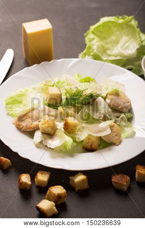 Classical Caesar salad with sliced chicken meat, fresh salad leaves, croutons and sauce in white round plate