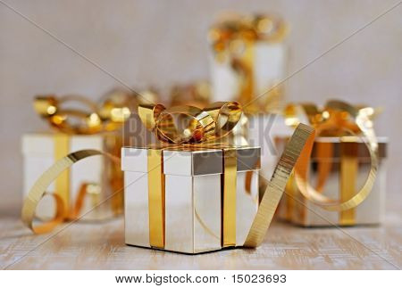 miniature silver and gold gift box ornaments on sweep of gift wrap with shallow dof