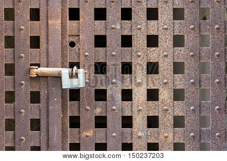 A padlock locking an iron grid door