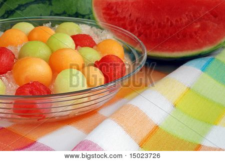 bowl of melon balls on crushed ice displayed on color coordinated tablecloth with seedless watermelon in the background