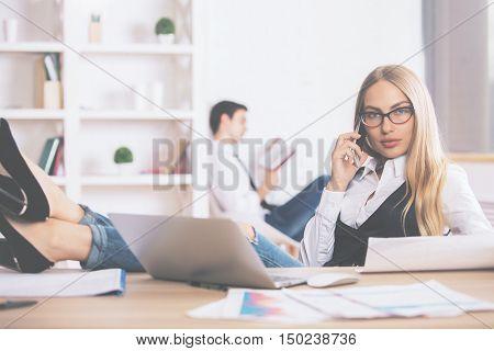 Female On Phone Doing Paperwork