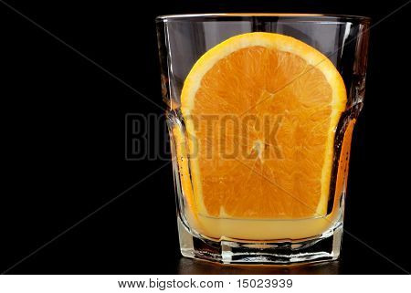 """freshly squeezed""  Close-up image of a fresh orange slice squeezed into a small juice glass on a reflective black surface with black background."