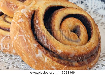 Freshly baked cinnamon rolls on bakery paper over a glass plate.  Close-up with shallow dof
