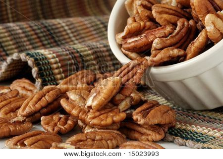 Macro still-life of fresh pecan halves spilling out of a small ceramic dish.  Shallow dof