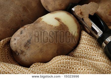 Close-up of fresh potatoes with potato peeler on coarsely woven fabric.  Textures emphasized with natural side-lighting