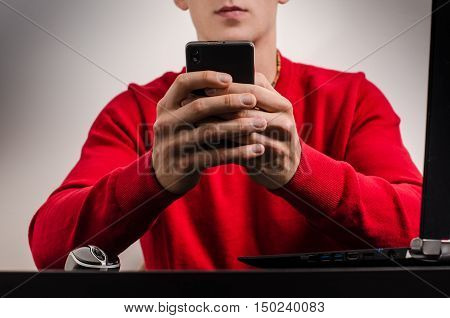 Businessman using a mobile phone indoor.Detail of hands and phone. Red sweater. Grey background.