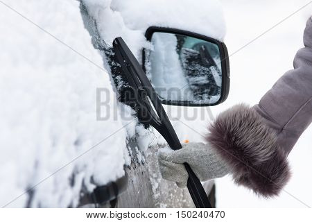 hand in mitten cleaning a car from the snow with a brush