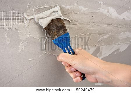 hand plastering wall with spatula repair conception