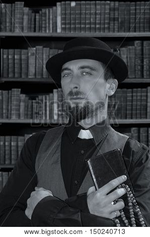 Young bearded priest holding bible on book background. Black and white photography