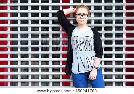 Young adult caucasian woman with blond hair tied in a bun in glasses wearing blue pants. tee-shirt and cardigan street fashion look