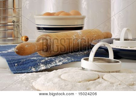 Vintage rolling pin with homemade biscuit dough.  Still-life with selective focus on flour sprinkled, rolling pin.  Bowl of eggs, flour sifter, and  lace curtains in soft focus in the background.