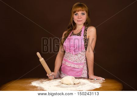 woman in apron preparing dough isolated on brown background