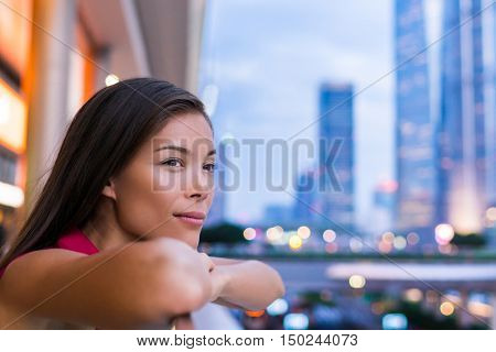 Urban city girl thoughtful and alone looking at city lights at night in Pudong, Shanghai, China. Multicultural Asian Chinese / Caucasian young woman professional enjoying time in financial district.