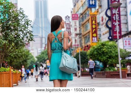 Happy girl walking on Nanjing Road, Shanghai city, China, one of the world's busiest pedestrian shopping street. Asian woman tourist visiting stores. Famous chinese attraction landmark.